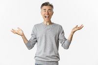 Image of shocked and frustrated man spread hands sideways, shouting and looking upset with something bad happened, standing over white background