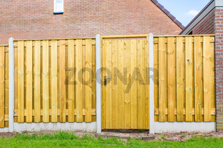 New wooden fence construction with door