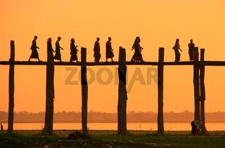 Silhouetted people on U Bein Bridge at sunset, Amarapura, Myanmar