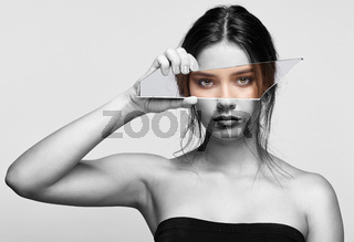 Girl covers her face with a shard of the mirror. Female with mirror shard in hand posing on gray background