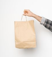 Male hand in plaid shirt twisted sleeve hand holding brown paper bag isolated on white background. Delivery concept. Paper bag for takeaway food. Square crop