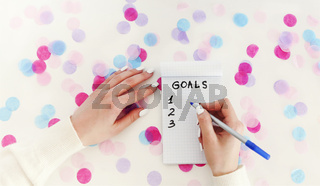 Crop woman writing goals in notepad