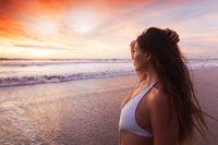 Woman in bikini by sea at sunset