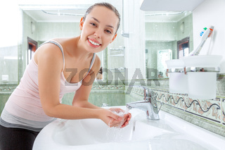 Young woman washing her face and hands with clean water in bathroom