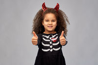 girl in black dress and devil's horns on halloween