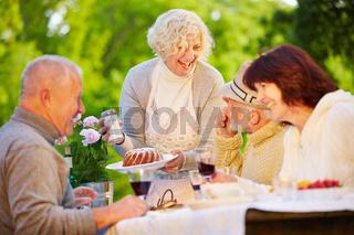 Gruppe Senioren beim Kuchen essen im Garten