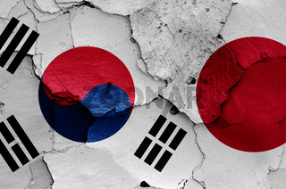 flags of South Korea and Japan painted on cracked wall