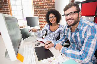 Smiling photo editors using digitizer in office