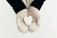 Snow heart snowball in girl gloved hands. Blurred background