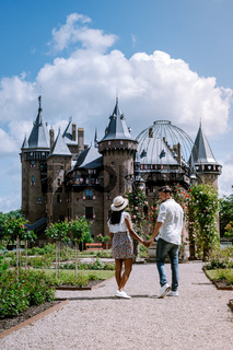 old historical castle garden,Castle de Haar Netherlands Utrecht on a bright summer day, young couple men and woman mid age walking in the castle garden