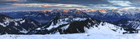 Amazing sunset alpenglow panorama view to snow covered mountain ranges and dramatic sky in cold winter. View from Riedberger Horn to Allgau Alps Mountains. Bavaria, Germany.