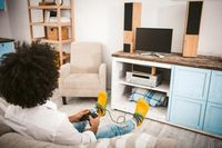 Stylish guy plays computer games sitting on couch. Young unrecognizable man with afro hairstyle in yellow slippers relaxing in home interior. Home alone concept. Rear view. Toned image