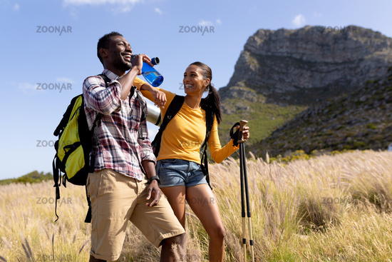 Fit afrcan american couple wearing backpacks nordic walking with poles drinking water in mountain co