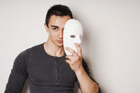 young man taking off white mask revealing face and identity