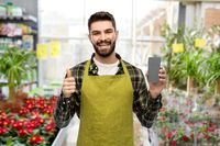 seller with phone shows thumbs up at flower shop