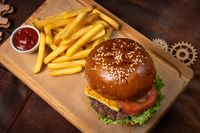 Top view. Beef burger are served with french fries on a decorative wooden board with tomato sauce with wooden decorative pieces of simple mechanism. Restaurant, Fast food concept. Street food concept