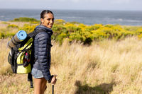 Portrait of fit african american woman wearing backpack nordic walking on coast