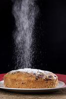 Puderzucker fällt auf einen Kuchen