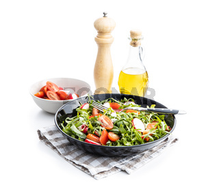 Fresh arugula salad with radishes, tomatoes and red peppers.