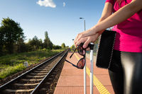 Summer train journey. A woman is standing on the railway platform and holding sunglasses in her hand.