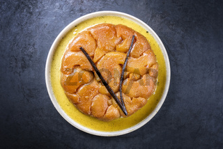 Traditional French tarte tatin with apples and vanilla offered as top view on a modern design plate with rustic background