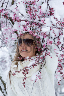 Woman by cherry blossom tree in snow