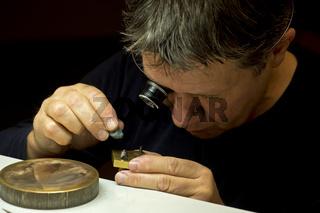 Uhrmacher poliert ein Teil einer Armbanduhr