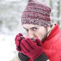 Mann im Schnee trinkt Tasse Tee