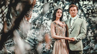 Gorgeous lady in long evening dress with tiara on a head and handsome man in classic suit. Young couple in love pose on nature looking at camera holding hands photo shoot outdoors. Bride groom concept
