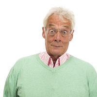 Senior man in green sweater surprised