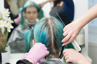 Back view of female head with emerald hair color and regrown hair roots. Woman sits in chair by mirror, two hairdressers combing client's hair