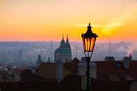 Sunrise behind an old street lamp over Lesser Town, Prague, Czech Republic.