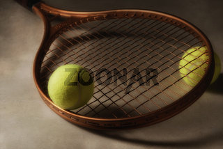 Closeup of a tennis racket and two balls on a hardcourt surface with strong side light.