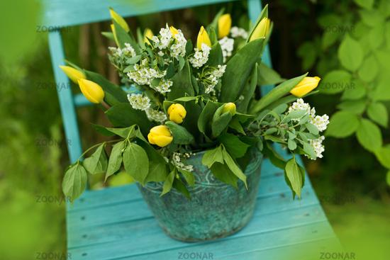 Tulip flower bouquet on a garden chair