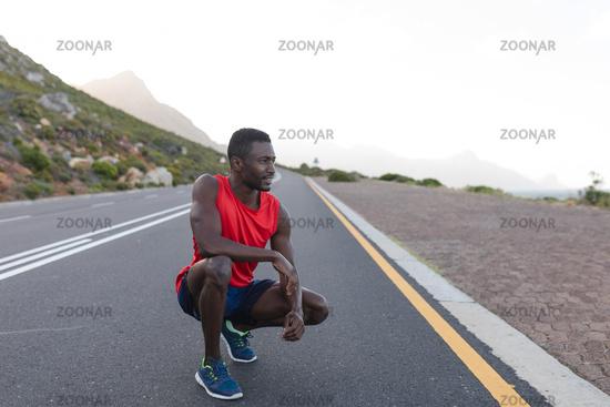 Fit african american man in sportswear stretching on a coastal road