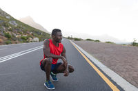 Fit african american man in sportswear stretching on a coastal road