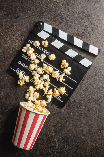 Sweet popcorn in cup and clappeboard.