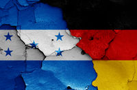 flags of Honduras and Germany painted on cracked wall