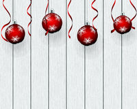Christmas baubles hanging on wooden background.
