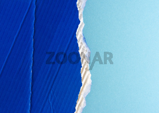ragged edges of blue cardboard on a light blue background