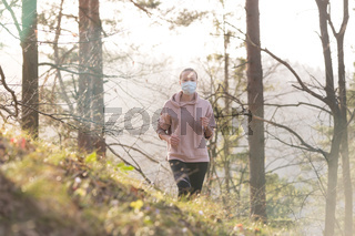 Corona virus, or Covid-19, is spreading all over the world. Portrait of caucasian sporty woman wearing a medical protection face mask while running in nature.