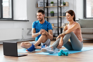 happy couple with laptop doing sports at home