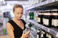 Woman choosing mineral water in grocery store