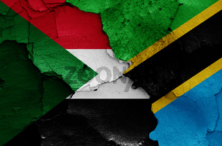 flags of Sudan and Tanzania painted on cracked wall