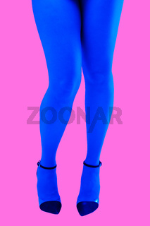 Close-up picture of woman's beautiful blue legs in high heels shoes on acid pink color background. Disco lights. Fasion. Surreal art. Funny modern art collage. Pop art. Zine culture. Front view.