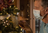 Senior adult man wearing face mask holding a christmas ornament and remembering the past