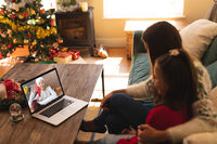 Woman and daughter sitting on couch having a videocall with woman in santa hat waving on laptop at h