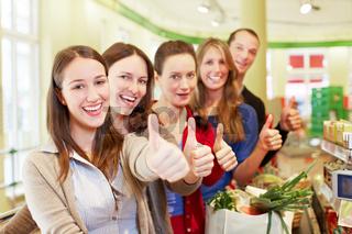 Kunden im Supermarkt halten Daumen hoch