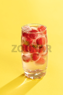 Frozen strawberries in a glass of water. Cold summer drink