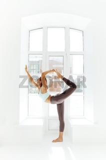 Flexible woman doing yoga at home